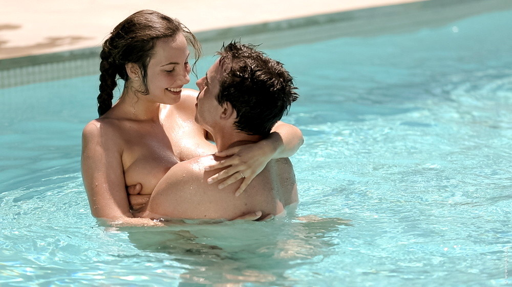 Sexy young couple relaxing near pool on a beach bed stock image